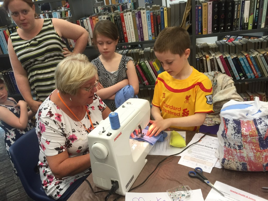 Jan showing a young family how the sewing machine works